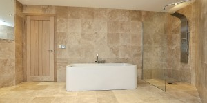 Modern wet room Bathroom, featuring natural travertine tiles.